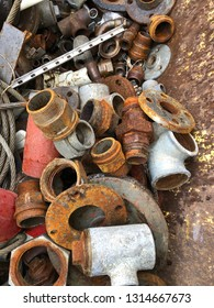 Rusty scrap from motor and plumbing parts in container at junk yard.