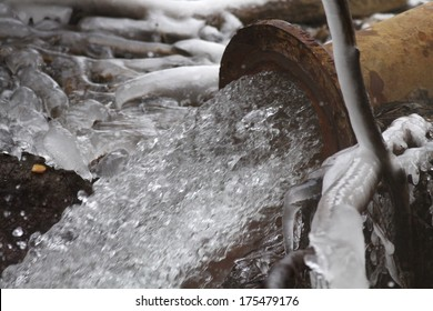 Rusty sewage pipe draining water during winter
