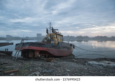 Rusty ship on the shore. Ship repair. Evening