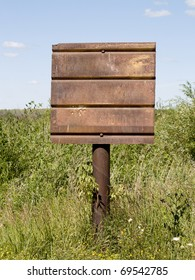 rusty signboard on a pillar, surrounded by green grass