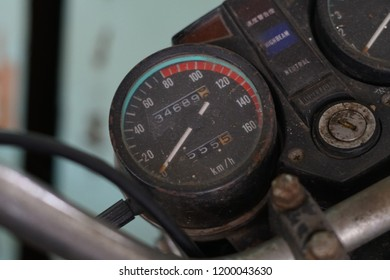 Rusty speed meters from vintage motorcycle with blurry handle and background