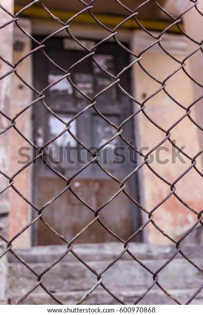 Rusty steel chain link or wire mesh as boundary wall. There is door behind the mesh.
