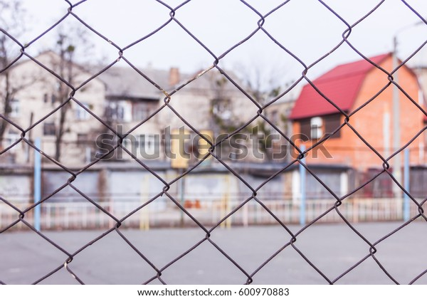 Rusty steel chain link or wire mesh as boundary wall. There is yard to the house with a red roof behind the mesh. Best security