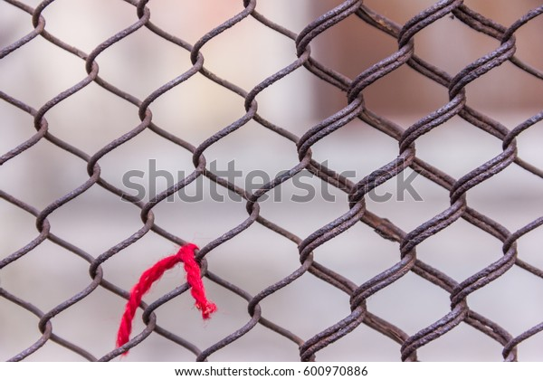 Rusty steel chain link or wire mesh as boundary wall. Red thread. There is still concrete block wall behind the mesh. Best security