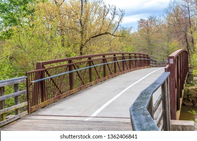 A rusty steel and concrete bridge on a treated lumber fitness trail in the spring forest