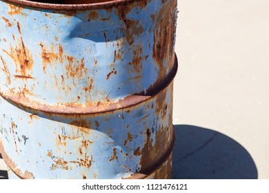 Rusty steel drum with peeling blue paint