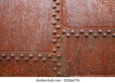 Rusty steel rivets on the steel sheet