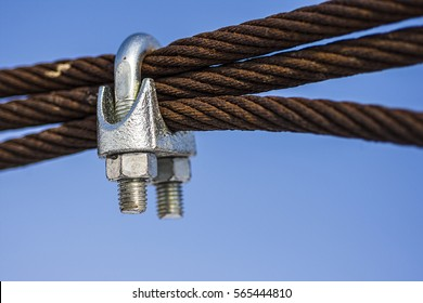 Rusty Steel Ropes with Shiny U-Bolt Clamp on Blue Sky Background. Business Teamwork Support Together Concept.