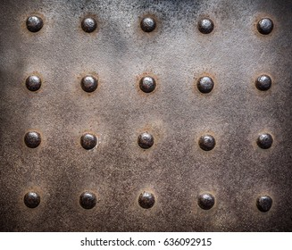 Rusty, studded cast iron vintage industrial plate background.