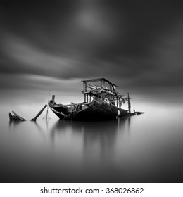 Rusty sunken boat on the sea in black and white long exposure fine art