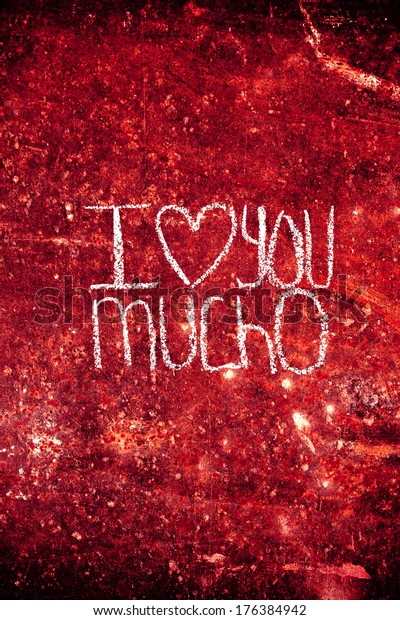 """Rusty texture in vertical written with chalk. The phrase """"I love you mucho"""" is written in the texture. Ideal for greeting cards."""