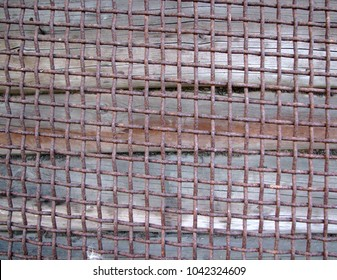 Rusty thick heavy intertwined metal vintage ancient grid surface on wooden background