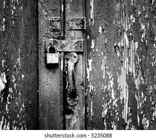 Rusty, unused lock on an old wooden door with peeling paint.
