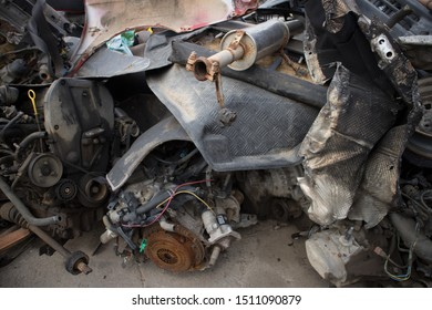 Rusty vehicle engines, exhausts, aluminum tread plate and other parts, stacked in an unarranged order. Awaiting dismantling, recycling or re-sale. At a car cemetery. Kozani, Greece.