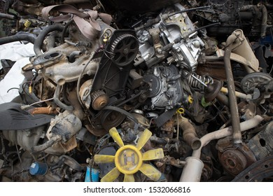 Rusty vehicle engines, exhausts, machine straps, a fan and other parts, stacked in an unarranged order. Awaiting dismantling, recycling or re-sale. At a car cemetery. Kozani, Greece.
