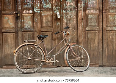 Rusty vintage bicycle in front of the old rustic house.On the door have many text. Classic bike and old wood house decorated perfectly look like retro style