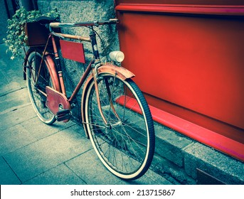Rusty vintage red bicycle leaning with on red wooden board (useful for entering a text advertisement, menu etc) and carrying plants in wooden box as decoration. Retro aged photo.