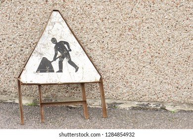 A rusty warning sign for roadworks, on a pavement in Scotland