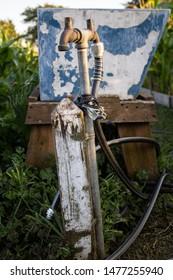 A rusty water spigot in an old garden.