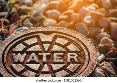 rusty water supply lid on ground with reflection and sunlight effect, rusty sewer cover on ground, steel water pipeline system, underground infrastructure, public utility on road of rock ground