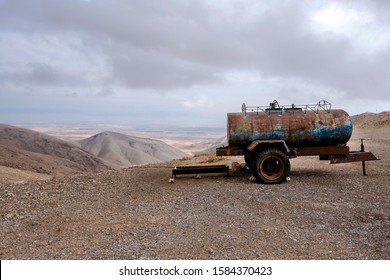 Rusty water tanker truck placed on the side of the gravel road in the desert, near Jericho city. West Bank