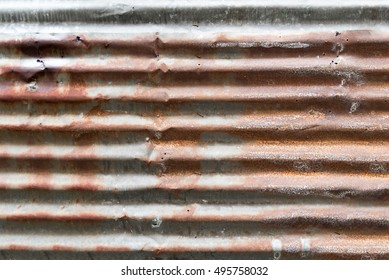 rusty and weathered looking piece of corrugated metal iron plate