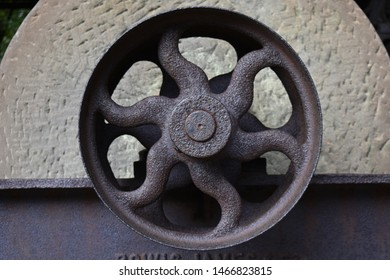 Rusty wheel with a stone plinth. Transport and motion, now stood still. 6 spoked iron wheel.