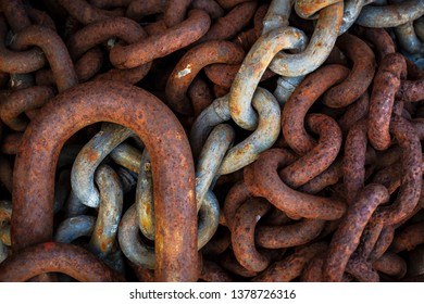 Rusty worn chain links in a pile. Corroded heavy chains at a harbor in detail. Good as background.