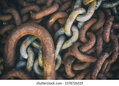 Rusty worn chain links in a pile. Filtered and good as background.