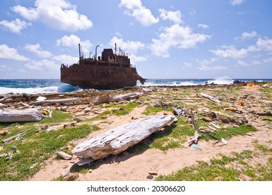 rusty wreck on little curacao with rubbish washed on the shore line