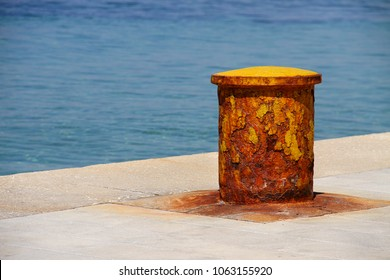 Rusty, yellow, metal, mooring bollard for ships at the port.