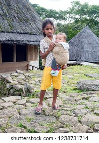 Ruteng Puu tradtional village, Flores, Indonesia - August 2018: Young girl taking care of little baby