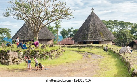 Ruteng Puu tradtional village, Flores, Indonesia - August 2018: Scene of Asian family making a visit to the local graves of their ancestors. A modern-times small community of tribesman