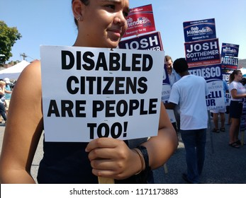 """Rutherford, New Jersey / USA - September 03 2018: At the 43rd Annual Rutherford Labor Day Street Fair, a young woman carries a sign that says, """"Disabled Citizens Are People Too!"""""""