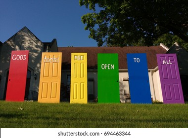 Rutherford, New Jersey/USA May 16 2017: On the lawn of a church, a word painted on each door - doors of different shapes, sizes, and colors - come together to say, `God`s Doors Are Open To All`.