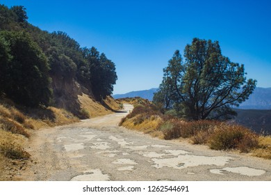 Rutted and pothole road leading into the mountains of southern California's Angeles National Forest.