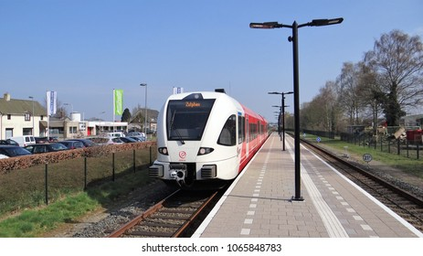 Ruurlo / Netherlands - April 10 2018: Arriva GTW diesel train drive by the small station of the dutch village Ruurlo in the Achterhoek. The destination of the red and white train is Zutphen.