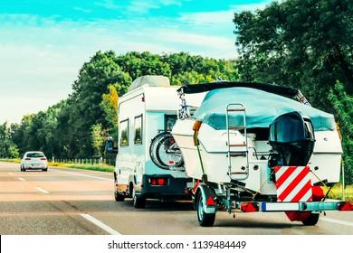 RV Camper Car with motor boat on Road. Caravan and motorhome in trip in Switzerland.