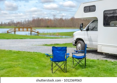 RV camper and chairs in camping, family vacation travel, holiday trip in motorhome