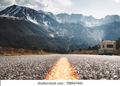 RV camper stands on side of road on background of huge mountain. Friends travel to motorhome on mountain road. Travelers rest on sidelines and enjoy mountain view. Vanlife