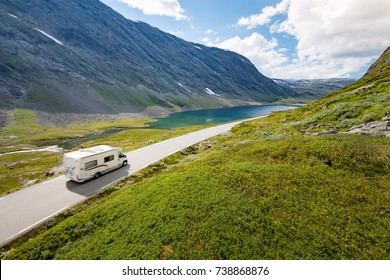 RV car in mountains of Norway, Europe. Auto travel through scandinavia. Blue cloudy sky and lake in background.