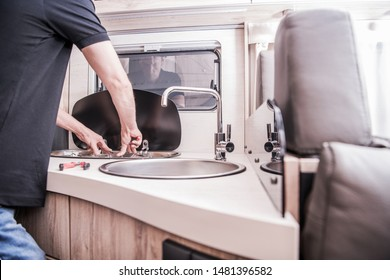 RV Motorhome Broken and Propane Leaking Stove Repair. Caucasian RV Technician Servicing Broken Stove Inside Modern Travel Trailer. Cooker Problem.