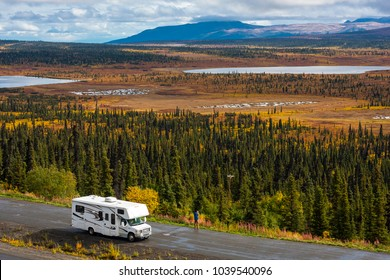 RV, motorhome, caravan parking next to a road in a parking lot in Alaska with spectacular, beautfiul background with lakes and conifer forest, blue sky and clouds
