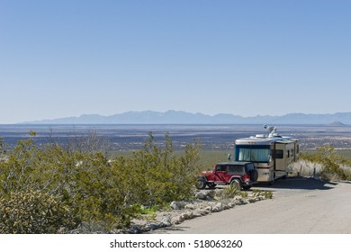 An RV and off road vehicle at a campground overlooking the valley below