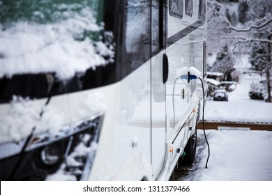 RV on the winter camping in Switzerland. Electricity plug on the camping car. AC power socket at a camping site. Power supply for a caravan. Winter camping with a RV in Switzerland.