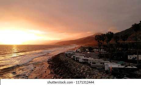 RV park (campground) at coast, California. Ocean. California during sunset. Aerial view, from above, drone flying over water.