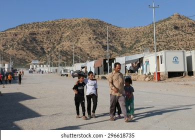 RWANGA REFUGEE CAMP, ZAKHO, KURDISTAN, IRAQ - 2015 JULY 13 - A family walking down the main street in Rwanga (rwanga refugee) camp