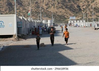 RWANGA REFUGEE CAMP, ZAKHO, KURDISTAN, IRAQ - 2015 JULY 13 - Young refugees walking down the main street in Rwanga (rwanga refugee) camp depict
