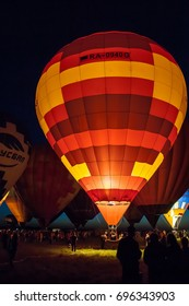 "RYAZAN, RUSSIA - AUGUST 2017: Hot air balloons in the annual Balloon Festival are illuminated for a ""Night Glow"" on the bank of Oka river August 12, 2017"