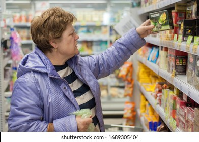Ryazan/Russia - March 27, 2020: a female customer buys products in a supermarket and puts them in a shopping trolley. Woman chooses tea